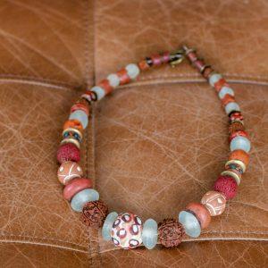 Blickfang in Terracotta: Zentrale Perle aus bemaltem Glas, Rudraksha Beads, antike Perlen aus Böhmen, Ton- und Recyclingglasperlen aus Westafrika