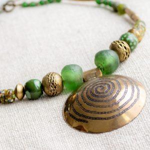 Eye catcher: Messinganhänger mit Spiralsymbol aus West-Afrika gerahmt von grünen Recyclingglas-, Keramik- und Bronzeperlen