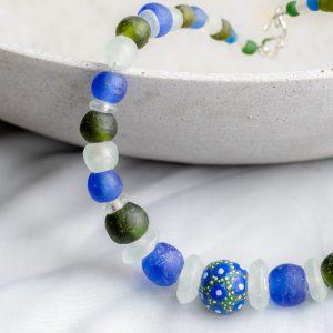 Handbemalte Mittelperle, gerahmt von blauen, grünen und transparenten Recyclingglasperlen aus Ghana